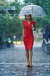 Young woman in a red elegant dress with an umbrella walking thoughtfully on a rainy day on a cobbled city street