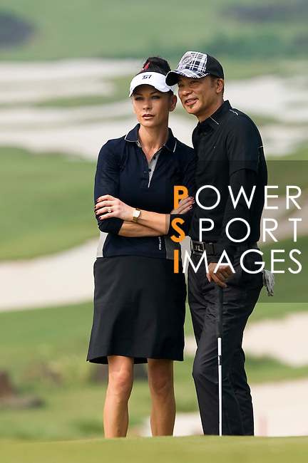 HAIKOU, CHINA - OCTOBER 31:  Catherine Zeta-Jones and Hong Kong actor Simon Yam talk on the 8th hole during day five of the Mission Hills Start Trophy at Mission Hills Resort on October 31, 2010 in Haikou, China.  The Mission Hills Star Trophy is Asia's leading leisure liflestyle event and features Hollywood celebrities and international golf stars. Photo by Victor Fraile / The Power of Sport Images