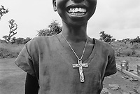 Uganda. West Nile. Adjumani. Ogujebe is distant 15 km from Adjumani and is a transit camp for refugees from South Sudan. A young girl, wearing a necklace with Jesus Christ on the Holy Cross, laughs and has fun. West Nile sub-region (previously known as West Nile Province and West Nile District) is a region in north-western Uganda. © 1989 Didier Ruef