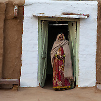 Bharatpur, Rajasthan, India.  Old Woman Standing in the Doorway of her House.  A Dupatta (Scarf) covers her head and shoulders.