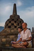 Borobudur, Java, Indonesia.  Man Praying at Sunrise.