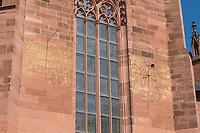 """Die Katharinenkirche in Oppenheim.<br /> Die Kirche gilt als eine der bedeutendsten gotischen Kirchen am Rhein zwischen Strassburg und Koeln. Ihre Errichtung erfolgte in Abschnitten im 13., 14. und 15. Jahrhundert.<br /> Die Kirche ist unteranderem fuer ihre Bleiglassfenster beruehmt, von denen viele noch im Original erhalten sind; so auch Fenster der """"Oppenheimer Rose"""".<br /> Bei Renovierungsarbeiten im Jahr 1959 wurde an der Suedseite der Fassade ein Portrait des damaligen Bundespraesidenten Theodor Heuss angebracht.<br /> Im Bild: Am Außenbau der Kirche angebrachte Sonnenuhren. Rechts die """"Planetenuhr"""". Sie hatte den Zweck, Grundlagen fuer horoskopische Untersuchungen zu bieten. <br /> 3.9.2021, Oppenheim<br /> Copyright: Christian-Ditsch.de"""