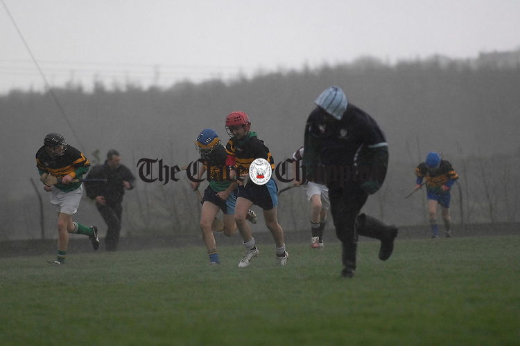 The Kilmihil and St Breckans teams race for shelter midgame during the U-14 a West Clare hurling final in Kilmihil. Photograph by John Kelly.