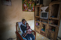 Uganda, Hoima. Hope Lydia Businge, 26 years, has a two year old daughter and runs a hair salon. At home she uses a BioLite cook stove that charges a light and mobile phone. At hom ewith her daughter.