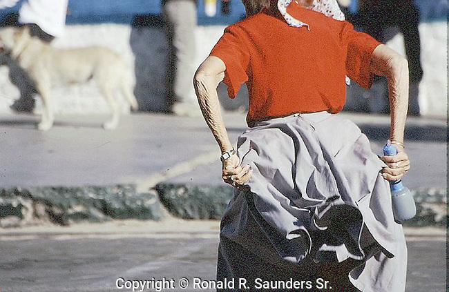 ELDERLY WOMAN DANCES ON MALECON DURING FIESTA