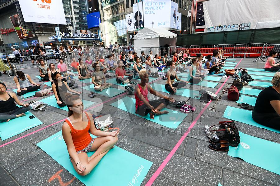 NEW YORK, EUA, 21.06.2017 - YOGA-NEW YORK - As pessoas participam de uma aula de yoga em grupo na Times Square, 21 de junho de 2017, na cidade de Nova York. Organizado pela Aliança Times Square, oito aulas de ioga foram realizadas na Times Square na segunda-feira para celebrar o solstício de verão. (Foto: Vanessa Carvalho/Brazil Photo Press)