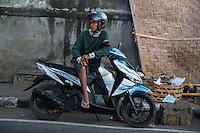 Jimbaran, Bali, Indonesia.    Young Man on his Motorbike, the Most Popular Mode of Transport in Bali.