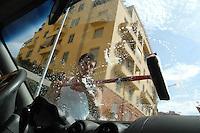 Immigrato mentre lava i vetri di un automobile ai semafori. .Immigrant while washing the windows of a car near the traffic lights..