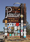 Paradise welcome sign on Skyway. <br /> The sign was built out of 30-foot tall salvaged bridge timbers in 1972. As with other city welcome signs it was festooned with emblems of community organizations. As a homage to Paradise's connection with the timber industry, it was topped with a 6-foot diameter halo fabricated from a saw blade. The sign burned to the ground on November 8, 2018.