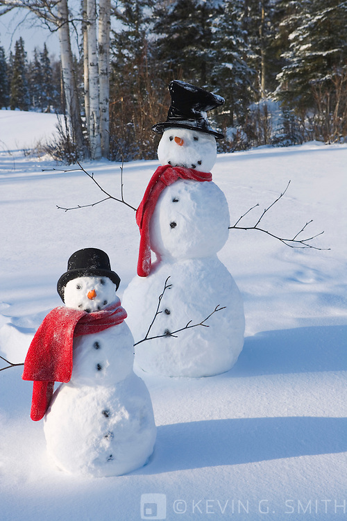 Parent and child snowmen both with red scarf and black top hat standing next to each other in a snow covered meadow, spruce forest in back ground.