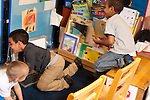 Education Preschool group of three boys physical play chasing each other in section of classroom