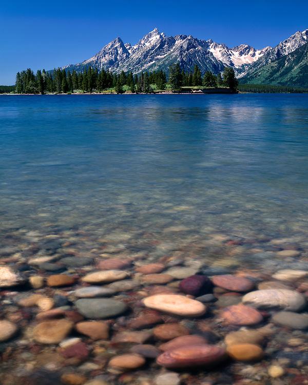 Rock-filled shoreline of Jackson Lake below the Teton Range; Grand Teton National Park, WY