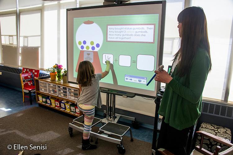 MR / Schenectady, NY. Zoller Elementary School (urban public school). Kindergarten inclusion classroom. Student (girl, 5) writes an addition sentence on digital whiteboard during math readiness lesson. MR: Cas12, War15. ID: AM-gKw. © Ellen B. Senisi.