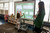 MR / Schenectady, NY. Zoller Elementary School (urban public school). Kindergarten inclusion classroom. Student (girl, 5) writes an addition sentence on digital whiteboard during math readiness lesson. MR: Cas12, War15. ID: AM-gKw. © Ellen B. Senisi.