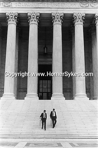 """WASHINGTON DC - USA 1969 EQUAL JUSTICE UNDER LAW. TWO IDENTICALLY DRESSED MEN IN BUSINESS SUITS AND CARRYING ROLLED UMBRELLAS WALK DOWN  """"Equal justice under law"""" is a phrase engraved on the front of the United States Supreme Court building in Washington"""
