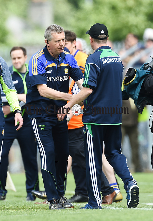 Donal Moloney, Clare joint manager offers his condolences to Limerick manager John Kiely following their Munster championship game in Ennis. Photograph by John Kelly.