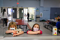 June Radder (left), 6, and Cylvia Feigelstein, 6, wait in line for their meals at the Boys and Girls Club of Western Pennsylvania in the Lawrenceville neighborhood on Friday February 19, 2021 in Pittsburgh, Pennsylvania. (Photo by Jared Wickerham/Pittsburgh City Paper)
