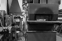 """26 è il numero atomico del ferro. <br /> La parola """"ferro"""" si utilizza per individuare leghe di più materiali, una perfetta commistione tra materie diverse: una sorta di equilibrio perfetto tra percentuali di metalli: elementi tenuti insieme, fusi e legati per sempre da ciò che per convenzione distrugge e disinfetta: il fuoco.<br /> """"VENTISEI"""" è un progetto fotografico durato 5 anni (2010-2015) nell'officina di Antonio Elia, fabbro artigiano di Poggiardo specializzato nella lavorazione artistica del ferro battuto. Vincitore di numerosi premi ottenuti al Concorso Internazionale di Disegno e Progettazione e al Campionato del Mondo di Forgiatura, Antonio è l'unico concorrente nella storia della manifestazione, nata nel 1973, ad aver partecipato a tre edizioni e ad aver vinto quattro premi.<br /> Un talento, quello di Antonio, alimentato dal padre Salvatore, fabbro artigiano anche lui, e da una passione travolgente, da una perfetta commistione tra manualità e creatività, che lo ha portato a primeggiare, unico italiano e più giovane di tutti, tra i migliori maestri del ferro battuto del mondo.<br /> <br /> Il progetto nasce dalla percezione che il ferro produce il ferro: dalla materia prima, (qualunque forma abbia: polvere di ferro, barrette, lamine) la mano dell'uomo riesce a creare quello che sarà un prodotto destinato ad un utilizzo nuovo o anche ad un attrezzo in ferro che servirà a costruire altri attrezzi in ferro: una condizione inanimata di genitorialità dello strumento verso altri strumenti.<br /> Il progetto fotografico prova a raccontare come la manualità crea plasticità provvisoria: la polvere che diventa oggetto solido. Il solido, modellato dal fuoco, cambia forma e torna ad essere solido solo dopo aver attinto alla creatività dell'artigiano. <br /> La sensazione che rimane, al termine di un ciclo di produzione alla fine del quale restano i segni tangibili su incudini e attrezzi, è che tutto ritorni nel silenzio da dove tutto ha avuto inizio."""