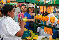 Antigua, Guatemala.  Vendor Selling Fresh Mangoes on a Stick.