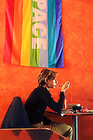 Switzerland. Ticino. Lugano. A woman eats her lunch in a restaurant. A peace (pace) flag, symbol of the opposition to the war in Iraq, is on the wall. A rainbow flag is a multi-colored flag consisting of stripes in the colors of the rainbow. The actual colors shown differ, but many of the designs are based on the traditional scheme of red, orange, yellow, green, blue, indigo and violet, or some more modern division of the rainbow spectrum (often excluding indigo, and sometimes including cyan instead). The use of rainbow flags has a long tradition; they are displayed in many cultures around the world as a sign of diversity and inclusiveness, of hope and of yearning. The peace flag is especially popular in Italy. 11.04.03 © 2003 Didier Ruef