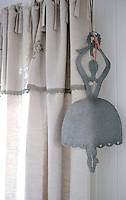 A zink ballerina hangs from the curtain rail in Mathilde's bedroom