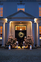 Inside the grand portico of this Grade I listed 17th century manor house the entrance door is decorated with a generous wreath and a pair of Christmas trees