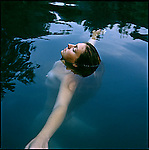 Young woman floating in swimming pool