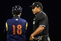 Umpire Jose Matamoros explains a call to manager Johnny Rodriguez (18) during a game between the State College Spikes and Batavia Muckdogs August 23, 2015 at Dwyer Stadium in Batavia, New York.  State College defeated Batavia 5-3.  (Mike Janes/Four Seam Images)
