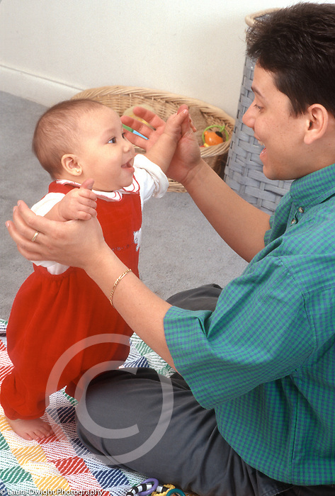 7 month old baby girl held in standing position by father happy interaction vertical