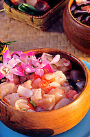 "Island style """"poke,"""" seasoned raw fish in a wooden bowl with an orchid garnish"