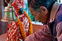 Kathmandu, Nepal.  Worshiper at a Shrine to the Hindu God Hanuman, the Monkey God, in a Neighborhood Temple.