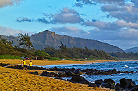 A couple takes in the view of the Sleeping Giant (or Nounou Mountain) just after sunrise at Kawailoa Bay on the east shore of Kaua'i.