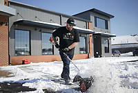 Matthew Phelt uses a snowbroomto clear the snow from a parking lot, Thursday, February 18, 2021 at Heritage Indian Motorcycle of Northwest Arkansas in Rogers. Check out nwaonline.com/210219Daily/ for today's photo gallery. <br /> (NWA Democrat-Gazette/Charlie Kaijo)