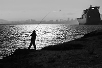 An angler in silhouette late on a summer afternoon, casting into San Francisco Bay with ships anchored at the former Naval Air Station Alameda in the background.