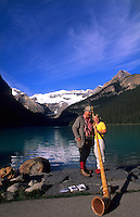 Lake Louise Banff, Canada. Swiss Alphorn player with tourist.
