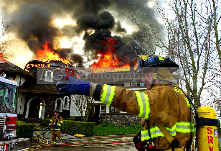 A san Ramon Valley firefighter gestures to others as he works at the scene of a house fire on El Alamo Way in Danville, Calif., Tuesday morning Feb. 25, 2003. Most of the second story was destroyed by flames. Officials estimate the damage at $3 million.  Alan Greth/ Contra Costa Times)
