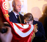 Conservative academic Kais Saied Wife  kisses the Tunisian flag as he celebrates his victory in the Tunisian presidential election in the capital Tunis on October 13, 2019. - Saied won a landslide victory in Tunisia's presidential runoff, sweeping aside his rival, media magnate Nabil Karoui, state television Wataniya said. It said he scooped almost 77 percent of the vote, compared to 23 percent for Karoui.