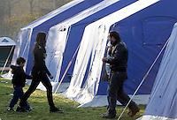 Sfollati tendopoli allestita in piazza d'Armi, all'Aquila, in Abruzzo, 8  aprile 2009, dopo il terremoto che ha colpito la regione..A woman walks with a child, past a man, in a tent-camp set up by the civil protection agency, in L'Aquila, central Italy, 8 april 2009, to put up survivors of the earthquake that hit the region Abruzzo..UPDATE IMAGES PRESS/Riccardo De Luca