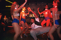 A man dances happily surrounded by costumed women during a performance at the Las Vegas-style nightclub which seems like an informal poor man's Tropicana. Often there is standing room only while a few early arrivals guard seats at tables crammed around a small dance floor. During some numbers, members of the audience are invited to participate and dance with the scantily clad women