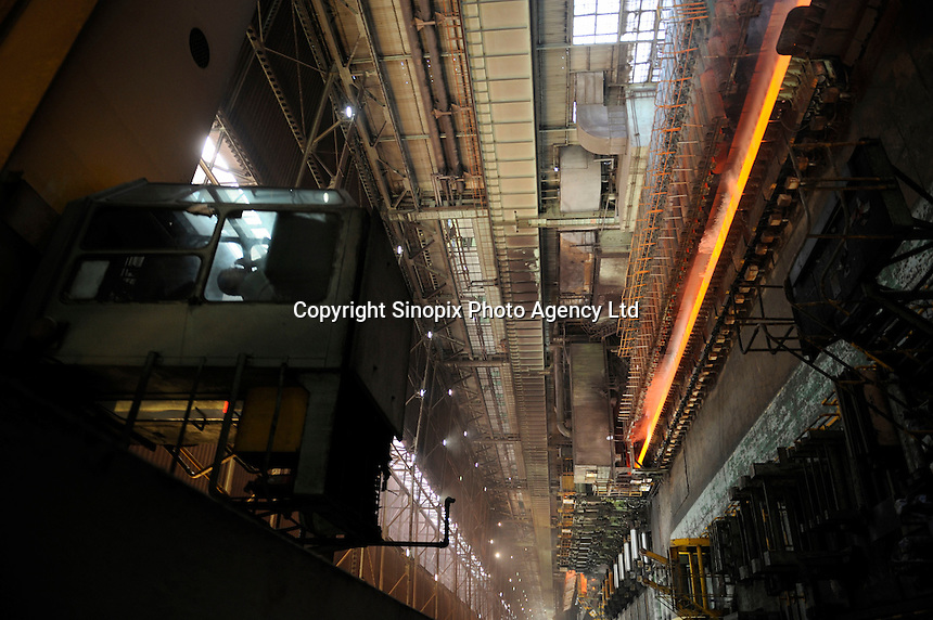 Molten hot plate steel being rolled at Shanghai Baosteel factory. Baosteel is the largest Chinese iron and steel conglomerate. It is a