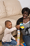 2 year old toddler boy with mother interaction playing with toys language development mother talking and involved flying toy vehicles over block tower African American vertical