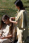 A Native American Indian woman braiding the hair of a young girl