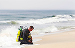 Asbury Park firefighter Brett Nielson pauses as he prepares to enter the surf to search for a 23-year-old man who disappeared after witnesses said he became caught in a rip current at the city's 2nd Avenue beach.  Nielson located the victim's body in 15 feet of water minutes later.