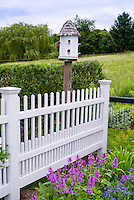 Bird house, fence, blue sky and clouds