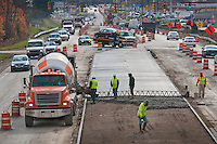 Construction workers pour concrete into the median divider  on Westerville road at the I-270 interchange. Work continues on the road beneath the interstate bypass overpass to replace the roadway, median, and  curbs. More construction further down  Westerville Road enlarges the Dempsey Road interchange and widens the road in front of businesses before the Alum Creek bridge. The city of Westerville is also changing the South State Street intersection at  Huber Village Blvd. for wider lanes and an improved traffic pattern.