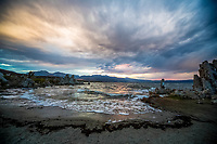 A fine art landscape image of sunset colors reflecting on stormy incoming surf at Mono Lake, California.  The waters develop foam from the alkaline pH of the lake and create an ocean-like surf design on the lake beach.