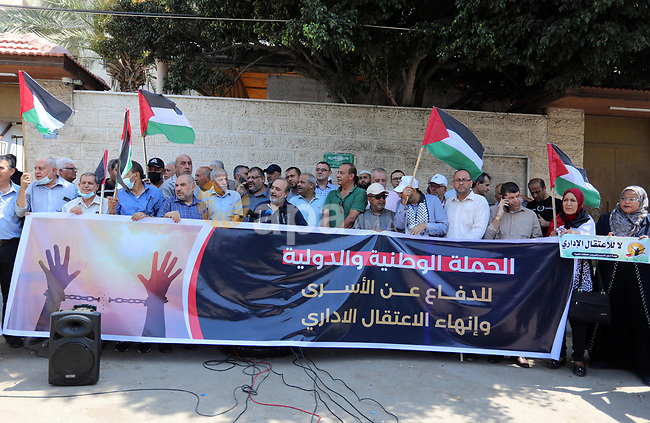 Palestinian members of the National and Islamic forces, take part in a protest to show solidarity with prisoners on hunger strike in Israeli Jails, in front of the headquarters of Red cross in Gaza city on August 08, 2021. A total of 13 Palestinian prisoners in Israeli detention currently remain on hunger strike in protest of their unfair administrative detention without a charge or trial, according to the Detainees and Ex-Detainees Affairs Commission. Photo by Ashraf Amra