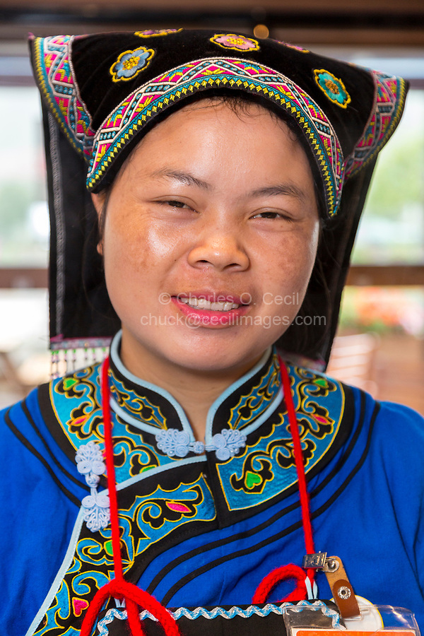 Guizhou, China.  Young Han Chinese Woman in Bouyei Dress, working in a Roadside Rest Stop.
