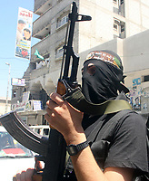 "A Palestinian gun men threw the funeal of Hamas militant Mohammed al-Batniji during his funeral in Gaza August 8, 2007. Israeli troops killed two Palestinian gunmen during a gun battle in the southern Gaza Strip on Wednesday, residents, ambulance workers and army officials said. ""photo by Fady Adwan"""