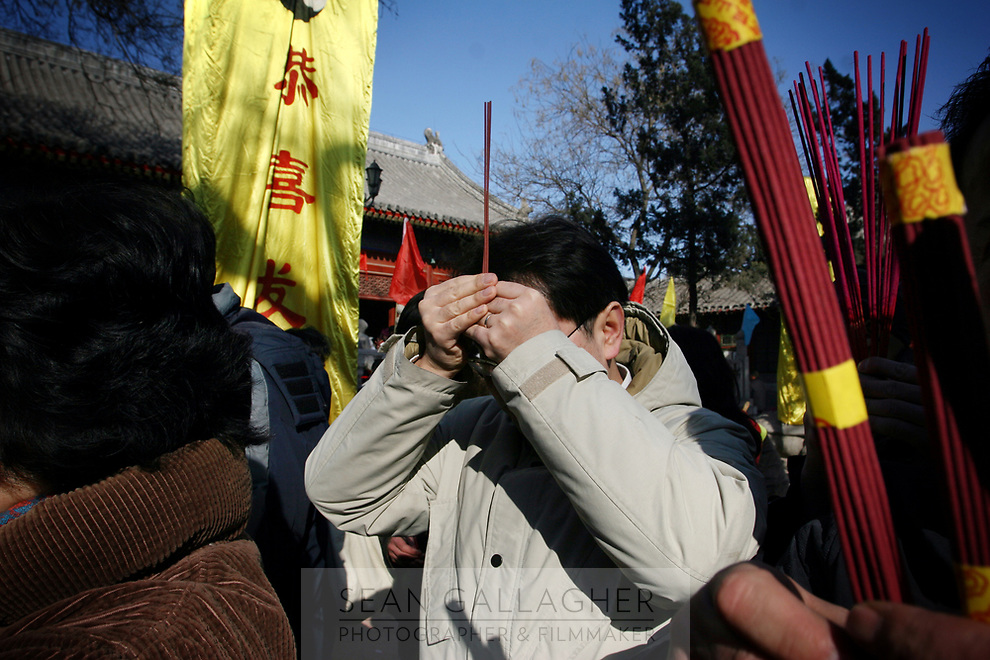 CHINA. A worshipper during Chinese New Year in Baiyun Temple in Beijing.  Chinese New Year, or Spring Festival, is the most important festival and holiday in the Chinese calendar In mainland China, many people use this holiday to visit family and friends and also visit local temples to offer prayers to their ancestors. The roots of Chinese New Year lie in combined influences from Buddhism, Taoism, Confucianism, and folk religions.  2008
